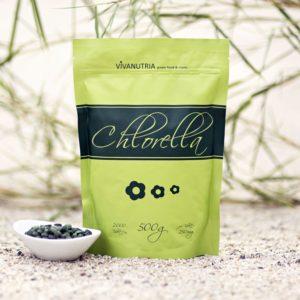 Chlorella Algen Tabletten und Tüte vor grauem Hintergrund