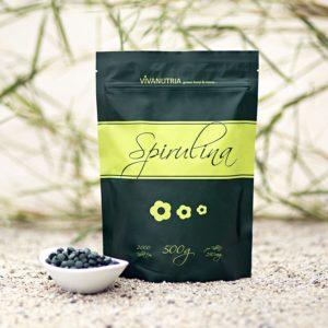 Spirulina Algen Tabletten und Tüte auf grauer Unterlage