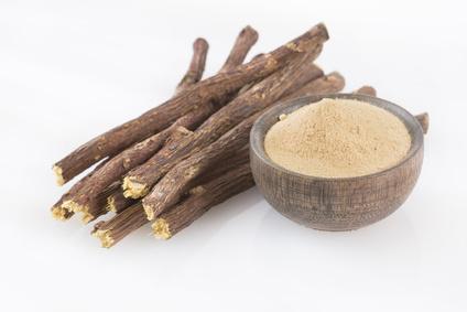 Süßholzpulver und -wurzeln auf weissem grund